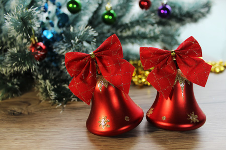 trumpery: Two beautiful red shiny bells closeup on the background of Christmas tree and tinsel on the wooden floor