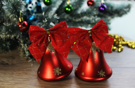 shiny floor: Two beautiful red shiny bells closeup on the background of Christmas tree and tinsel on the wooden floor