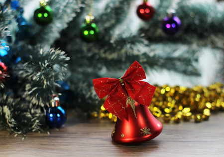 frippery: Two beautiful red shiny bells closeup on the background of Christmas tree and tinsel on the wooden floor