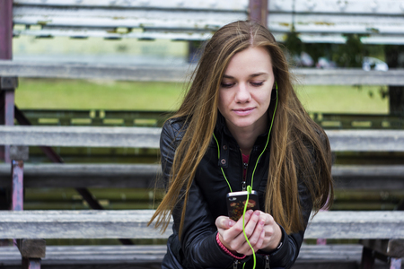 hark: Young beautiful girl look and listening music on your mobile phone on the old stadiums bench Stock Photo