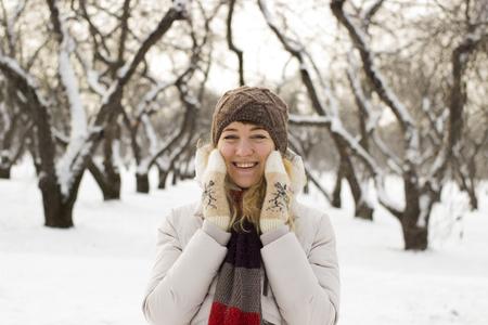 enjoys: Young beautiful girl close up in winter park enjoys snow fell Stock Photo