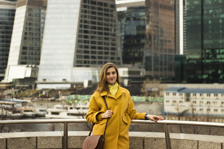 backround: Beautiful young woman stand on the high-rise buildings backround