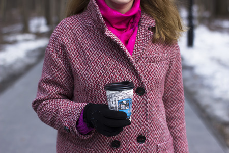 Beautiful young woman walk outdoor in park with plastick cup of coffee, that she takes in your hands