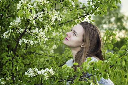 among: Portrait of beautiful young girl close up among a blossoming tree with green leaves outdoors Stock Photo