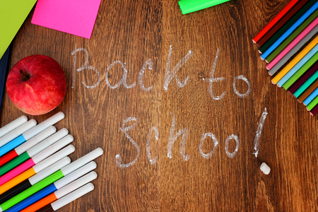 Colored pencils, felt-tip pens and markers, notebooks, stickers a red apple on the wooden background with the back to school inscription, top view.