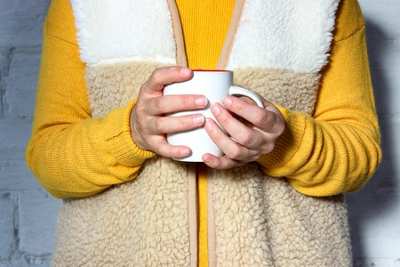 Woman holds a hot cup of tea and warms his hands.