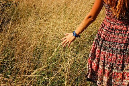 letting: Young beautiful girl walking in the field and runs hand through the high dry grass at summertime.