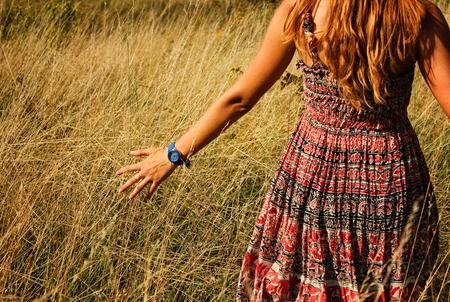 Het jonge mooie meisje lopen in het gebied en de looppas hand door het hoge droge gras in zomer.