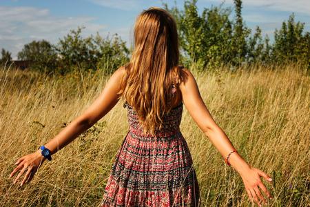 Het jonge mooie meisje lopen in het gebied en de looppas hand door het hoge droge gras in zomer. Stockfoto
