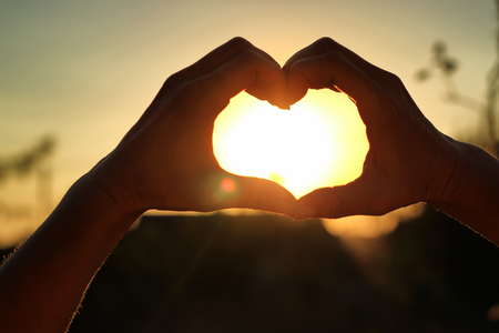 Womens hands are crossed in the form of the heart through which the sun rays make the way at the sunset Stock Photo