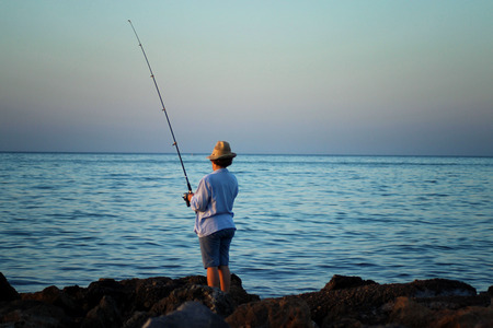 A woman in a hat is fishing with a fishing rod in her hand by the sea coast Stock Photo