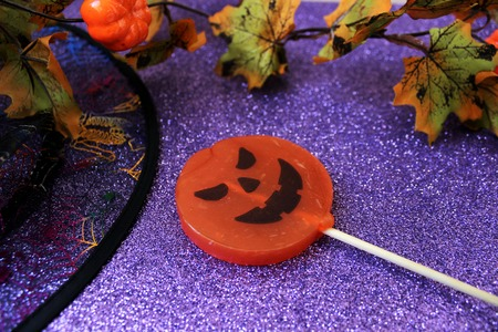 Candy in the form of a pumpkin for Halloween on the brilliant background with decorations for Halloween. Halloween background