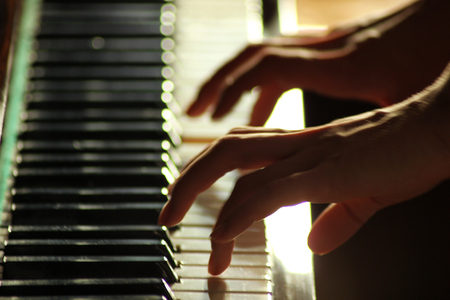 Fingers of young woman playing on the piano closeup. Soft and blur conception