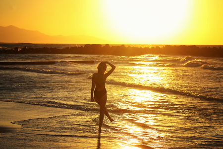 Silhouette of Young beautiful girl close up near the sea at the sunset Stock Photo