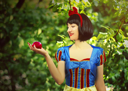 Young beautiful snow-white close-up keeps a red poisoned apple against the background of trees in the forest