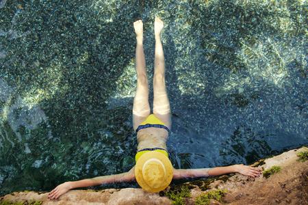 Young beautiful girl in yellow swimsuit lying in the water closeup Stock Photo