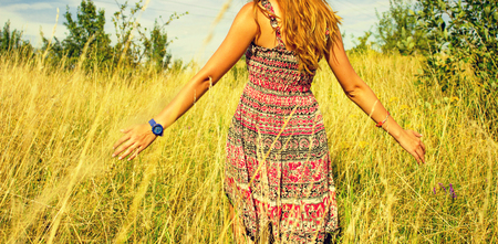 Young beautiful girl walking in the field and runs hand through the high dry grass at summertime Stockfoto