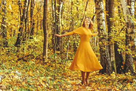 Young beautiful girl in a yellow long dress walks in autumn park with fallen leaves 写真素材 - 113611432