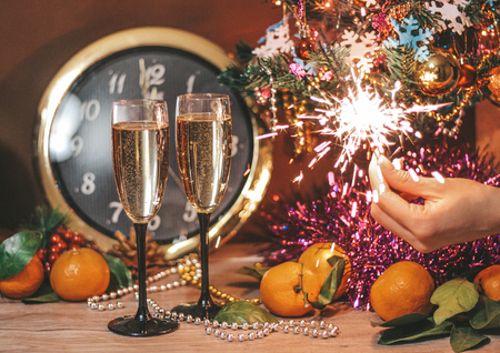 Christmas composition consisting of hours, the arrow of which is at 12 oclock, glasses of champagne with bubbles, sparklers in the hand of a girl, decorated Christmas tree, tangerines and other decorations Фото со стока