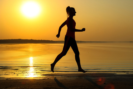 Silhouette of a young beautiful girl is running along the seashore on the orange sunset background.