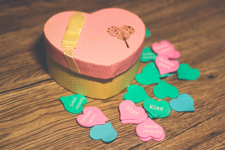 Gift pink box in the form of a heart filled with multi-colored small hearts on a wooden background