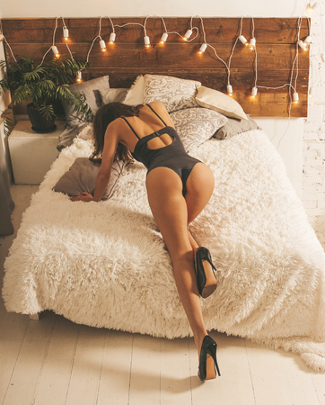 Young sexy girl in lingerie and black high heel shoes on the bed.