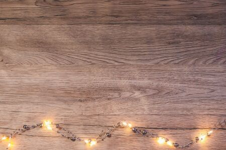 Brown wooden background with a luminous garland below. New Year flat lay with place for text. Banque d'images - 135503176