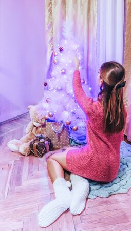 A girl in a pink dress and knitted socks decorates a white Christmas tree with pink balls and other decorations Stock Photo