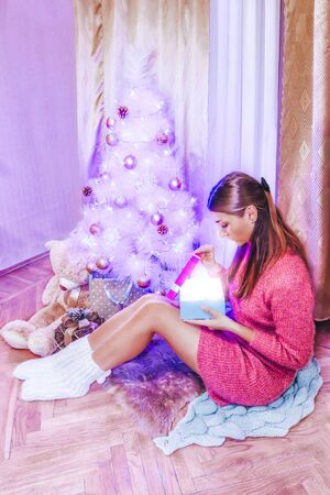 A girl in a pink dress and knitted socks under the tree opens a New Years gift
