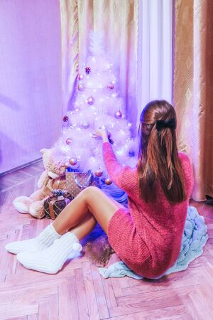 A girl in a pink dress and knitted socks decorates a white Christmas tree with pink balls and other decorations