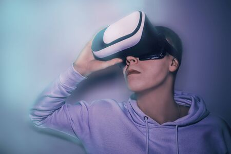 Young man looks into virtual reality glasses in neon blue light close-up