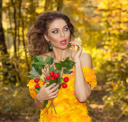 Portrait of a young beautiful woman in a dress made of autumn leaves in the park in autumn season with bouquet of flowers in her hands
