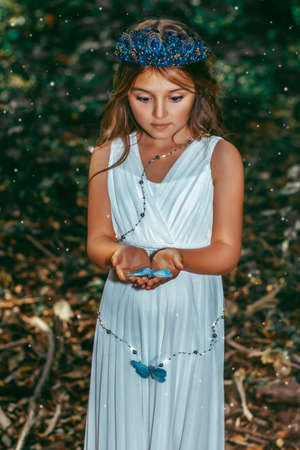 Cute little princess girl with blue butterflies in the forest. Art processing.