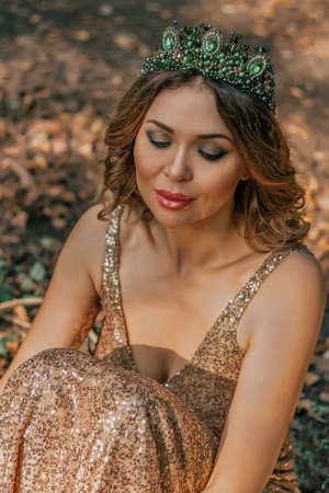 Beautiful woman in golden long dress in the forest background in autumn season. Stok Fotoğraf