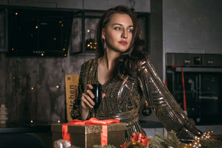 Young pretty woman close up with black glass of champagne on the festive decorations background.Christmas photo. Stok Fotoğraf