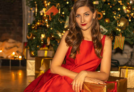 Young pretty woman in red dress closeup under the fir tree with Christmas decorations