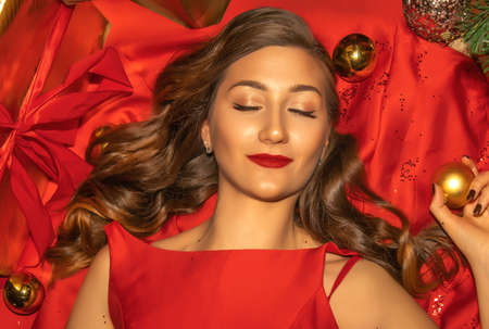 Young pretty woman in red dress closeup with Christmas decorations