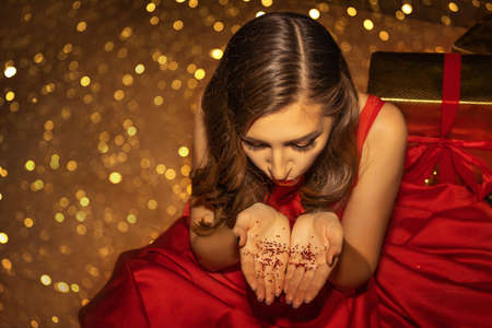 Young pretty woman brunette closeup is blowing the red glittered stars from her hands