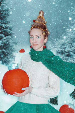 Pretty woman-fir-tree closeup with red Christmas balls in her hand on the snowy background.Art photo