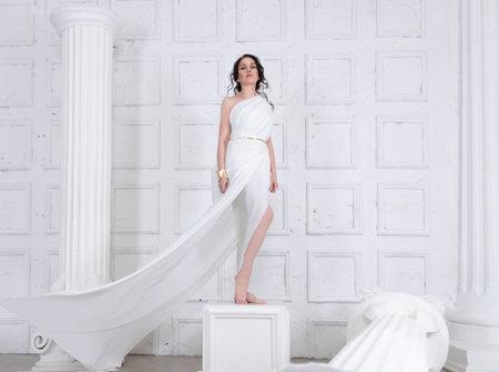 Beautiful Greek goddess woman close up among the white ancient ruins.Greek style woman