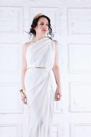 Beautiful Greek goddess woman close up among the white ancient ruins.Greek style woman.