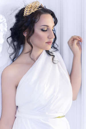 Beautiful Greek goddess woman closeup on the white ancient ruins background