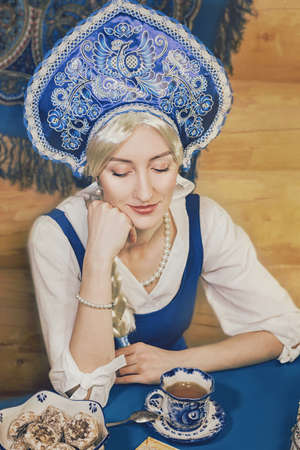 Russian beauty closeup is drinking tea with cookie and other delicious food