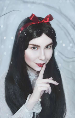 Young pretty woman with white skin and red lips is keeping the red poisoned apple.Snow white princess cosplay.Art photo