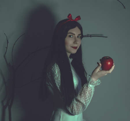 Young pretty woman with white skin and red lips is keeping the red poisoned apple on the branches background.Snow white princess cosplay.Art photo