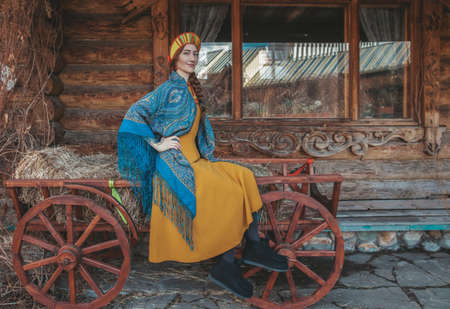 Russian beauty in traditional dress sits on a cart with hay. Stok Fotoğraf
