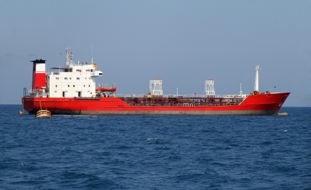 Red tanker designed for transporting crude oil is at anchor near the port photo