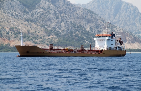 Oil tanker at the background of mountains photo