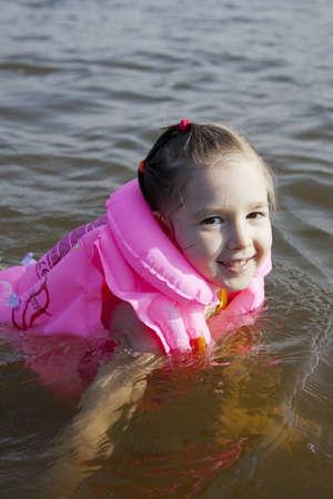 Mädchen im Wasser und gehen in das Lernen, wie man schwimmt Standard-Bild