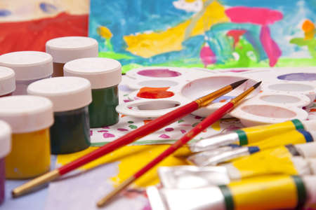 paints and brushes on the background of children photo